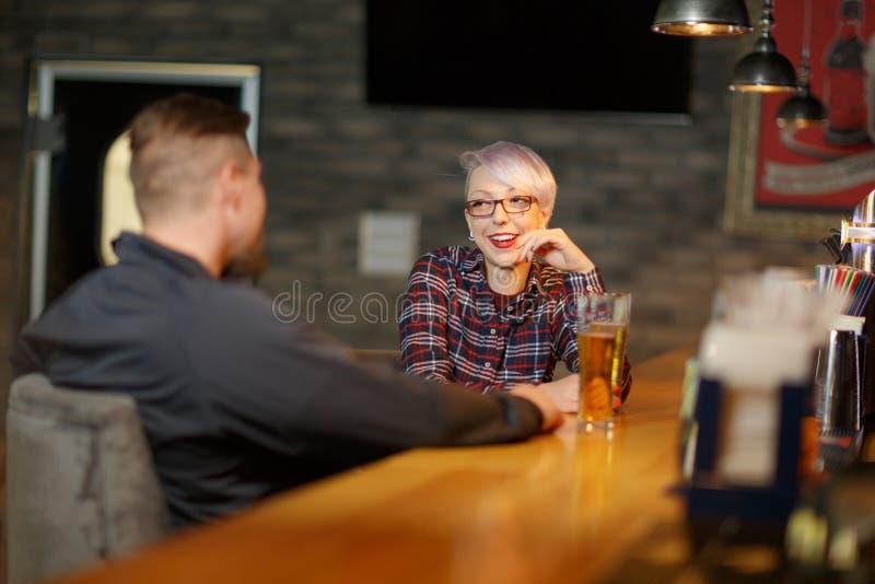 Una muchacha feliz, se sienta y habla en una barra con un hombre y bebe la cerveza dentro foto de archivo