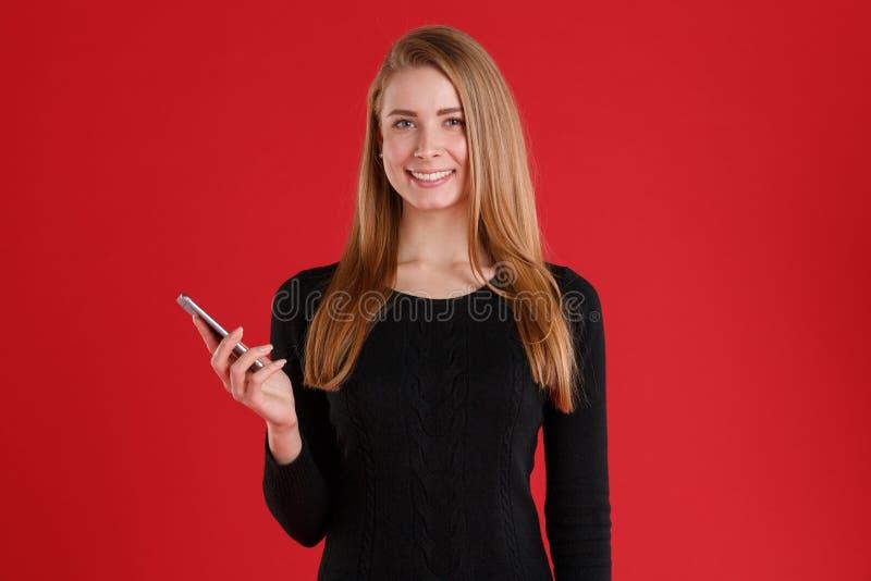 Una muchacha feliz, sonriendo y sosteniendo un teléfono móvil imagen de archivo