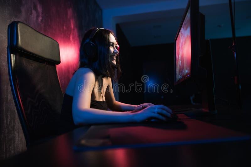 Una muchacha femenina linda del videojugador se sienta en un cuarto acogedor detrás de un ordenador y juega a juegos Vídeo vivo d fotos de archivo libres de regalías