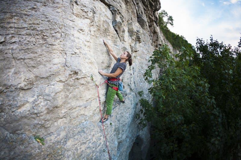 Una muchacha fuerte sube la roca imágenes de archivo libres de regalías