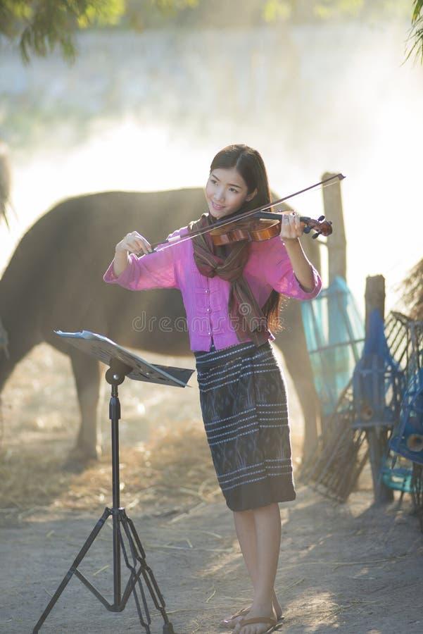 Una muchacha hermosa asiática que toca un violín imagenes de archivo