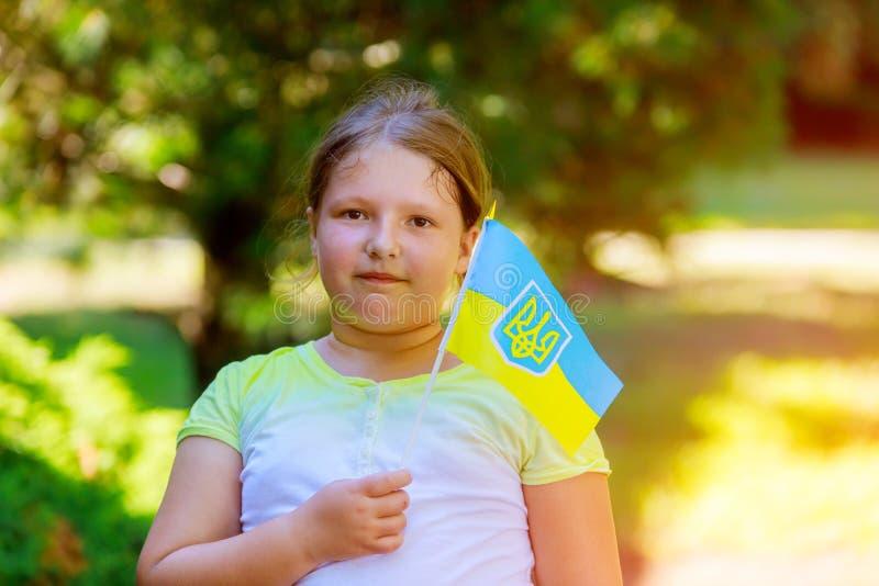 una muchacha hermosa con el amor que sostiene una bandera de Ucrania al día de verano imágenes de archivo libres de regalías