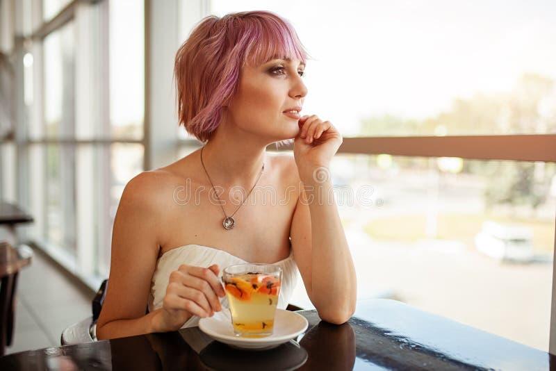 Una muchacha hermosa con el pelo pintado rosa se sienta en un restaurante cerca del té de consumición y de parecer de la fruta de fotos de archivo