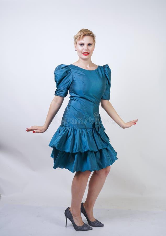 Una muchacha hermosa con una figura del tamaño extra grande vestida en un vestido retro lindo y soportes de la moda en un fondo b imagen de archivo