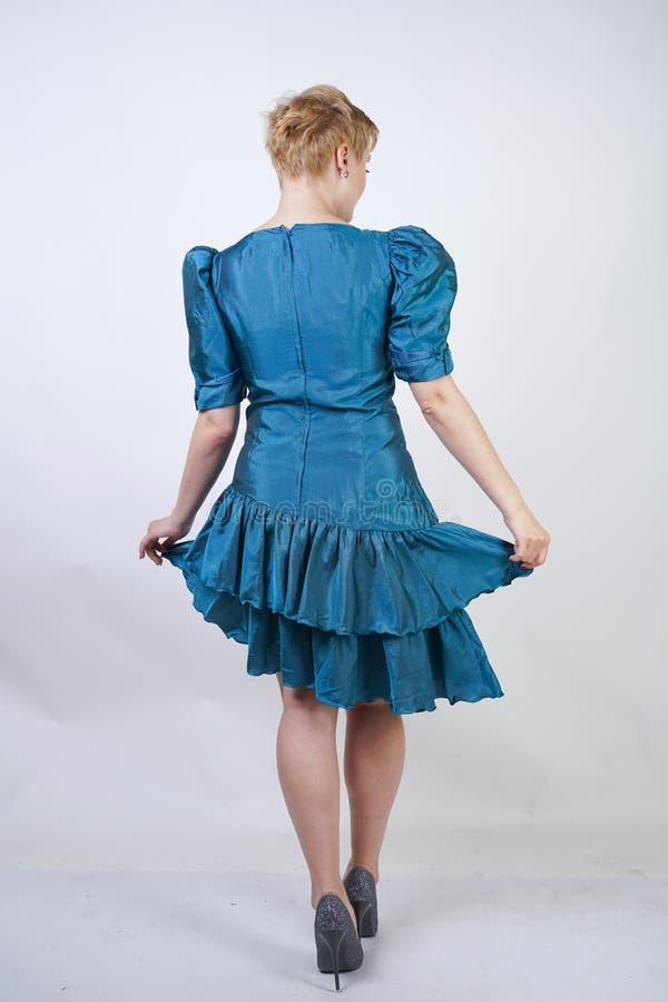 Una muchacha hermosa con una figura del tamaño extra grande vestida en un vestido retro lindo y soportes de la moda en un fondo b fotos de archivo