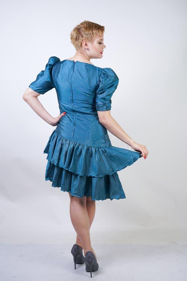 Una muchacha hermosa con una figura del tamaño extra grande vestida en un vestido retro lindo y soportes de la moda en un fondo b foto de archivo libre de regalías