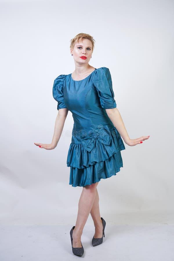 Una muchacha hermosa con una figura del tamaño extra grande vestida en un vestido retro lindo y soportes de la moda en un fondo b imágenes de archivo libres de regalías