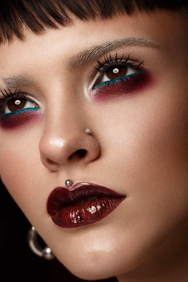 Una muchacha hermosa con maquillaje creativo del arte y pendientes en la cara imagen de archivo