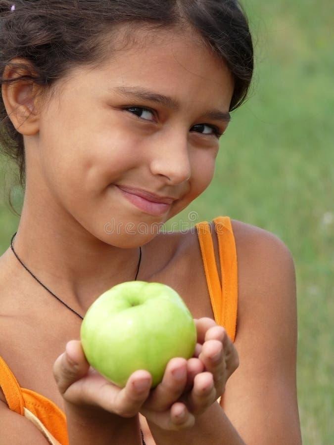 Una muchacha hermosa con una manzana verde fotografía de archivo libre de regalías