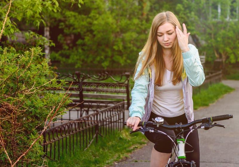 Una muchacha hermosa en una bicicleta ajusta su pelo imagen de archivo