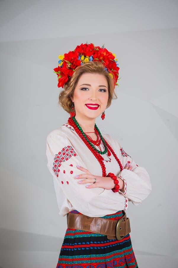 Una muchacha hermosa en traje ucraniano nacional Capturado en estudio Bordado y chaqueta Guirnalda Anillo de flores Labios rojos fotografía de archivo