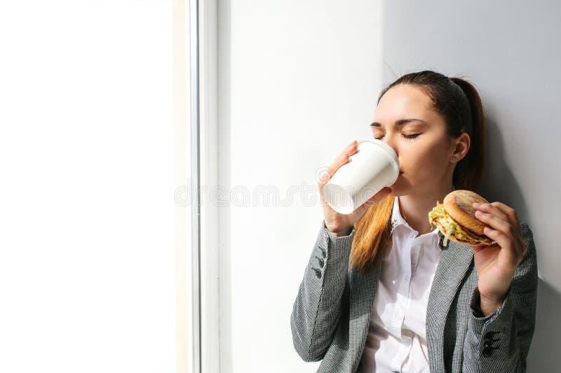 Una muchacha hermosa joven bebe el café al lado de una ventana y come una hamburguesa en una rotura entre el trabajo Alimentos de fotografía de archivo libre de regalías
