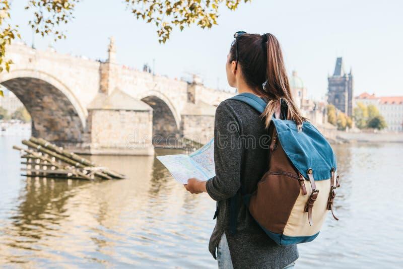 Una muchacha hermosa joven coloca y mira el mapa al lado del río de Moldava con la vieja arquitectura asombrosa de Praga imagenes de archivo