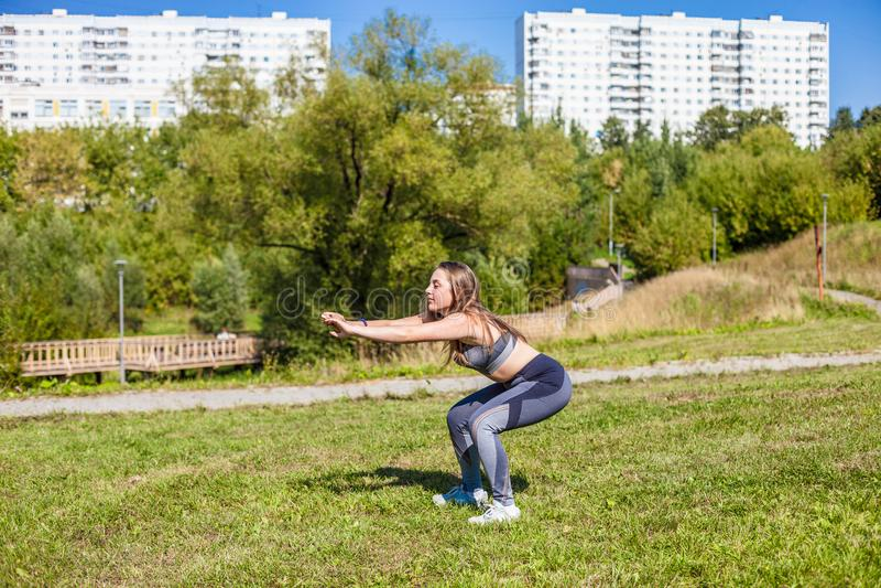 Una muchacha hermosa joven en una camiseta gris, pantalones grises y zapatillas de deporte haciendo deportes ejercita en la hierb fotos de archivo