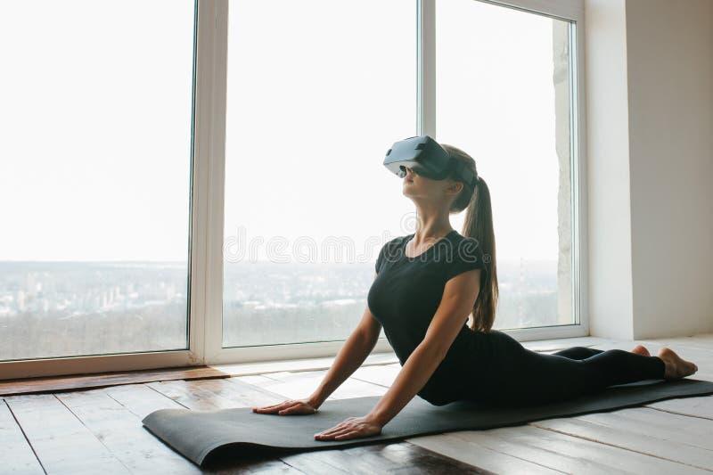 Una muchacha hermosa joven en vidrios de la realidad virtual hace yoga y aeróbicos remotamente Concepto futuro de la tecnología m fotografía de archivo