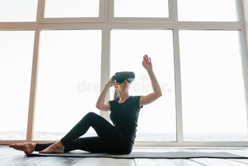 Una muchacha hermosa joven en vidrios de la realidad virtual hace yoga y aeróbicos remotamente Concepto futuro de la tecnología m fotos de archivo