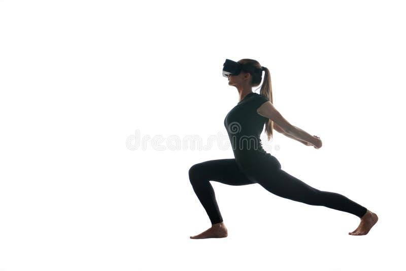 Una muchacha hermosa joven en vidrios de la realidad virtual hace yoga y aeróbicos remotamente Concepto futuro de la tecnología m fotografía de archivo libre de regalías