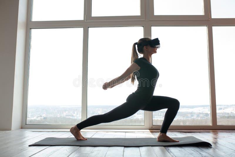 Una muchacha hermosa joven en vidrios de la realidad virtual hace yoga y aeróbicos remotamente Concepto futuro de la tecnología m imagen de archivo