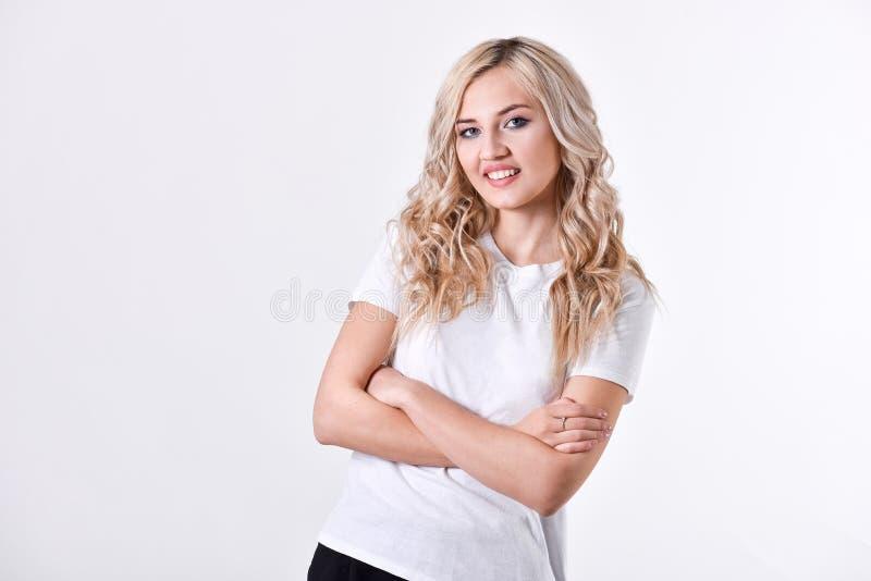 Una muchacha hermosa joven rubia se coloca con las manos dobladas, una camisa blanca, en un fondo blanco fotos de archivo