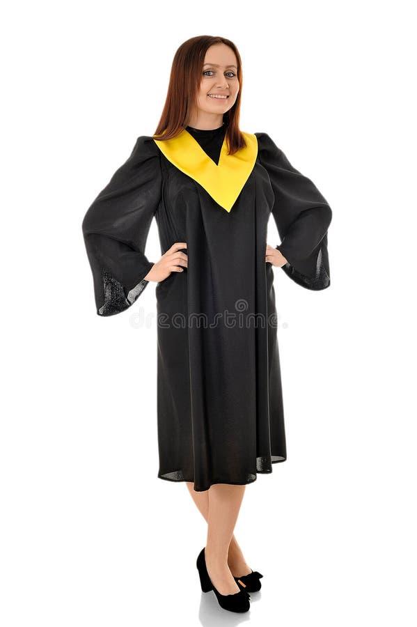 Una muchacha hermosa que se coloca en el vestido negro del graduado foto de archivo libre de regalías