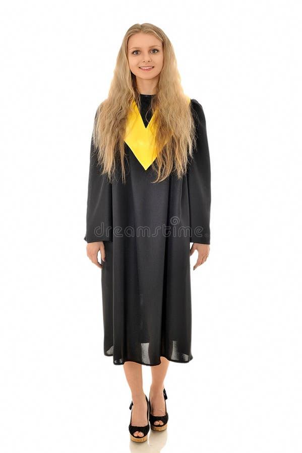 Una muchacha hermosa que se coloca en el vestido negro del graduado fotos de archivo libres de regalías