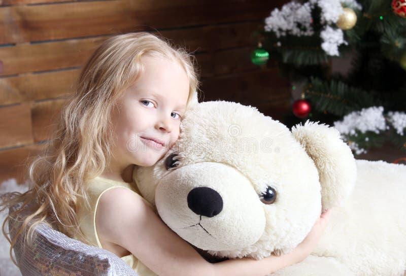 Una muchacha hermosa que se sienta debajo del árbol de navidad imagenes de archivo