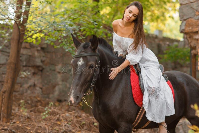 Una muchacha hermosa se está sentando en un caballo y lo está frotando ligeramente afuera imagenes de archivo