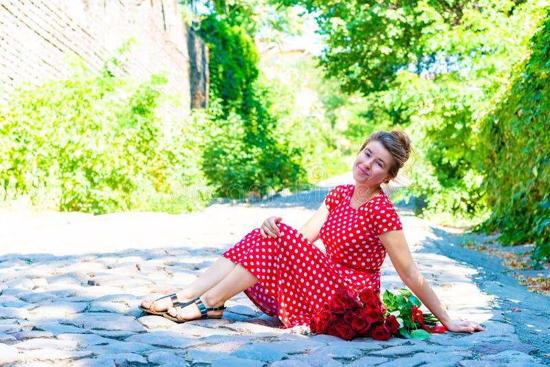 Una muchacha hermosa y atractiva se sienta en un camino del ladrillo, y un ramo de rosas rojas miente de lado a lado en el piso imagenes de archivo