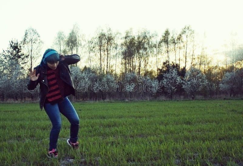 Una muchacha interesante en pelo azul, escucha la música y las danzas en el campo fotografía de archivo