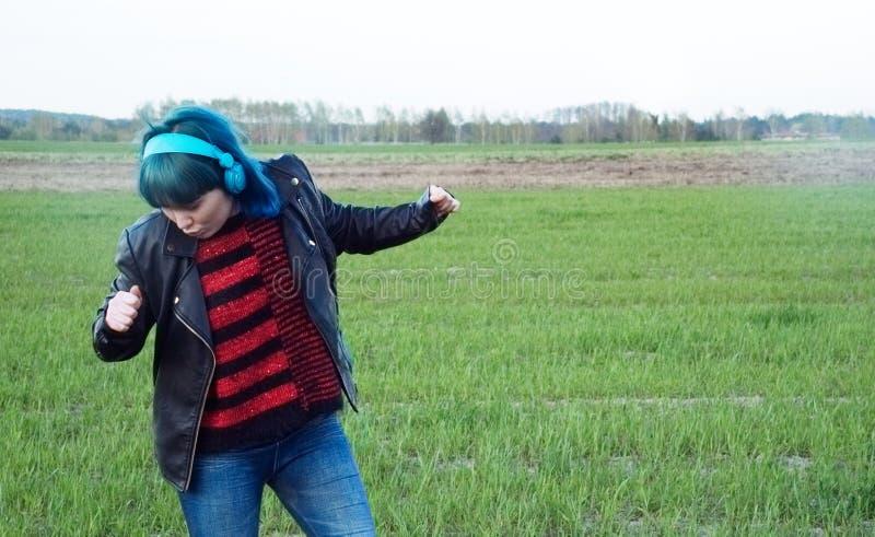 Una muchacha interesante en pelo azul, escucha la m?sica y las danzas en el campo fotografía de archivo