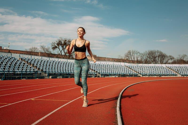 Una muchacha joven hermosa de la raza mixta está corriendo a lo largo de una rueda de ardilla en el estadio imágenes de archivo libres de regalías
