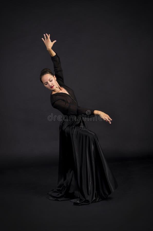 Una muchacha joven, sonriente en el traje negro que baila coreografía moderna imagen de archivo