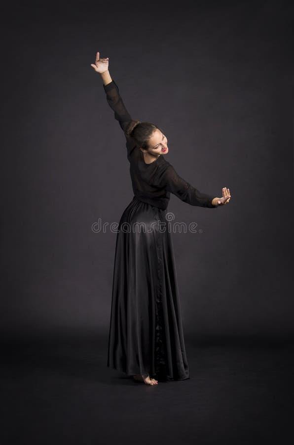 Una muchacha joven, sonriente en el traje negro que baila coreografía moderna imagen de archivo libre de regalías