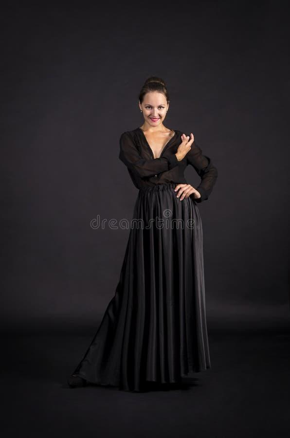 Una muchacha joven, sonriente en el traje negro que baila coreografía moderna fotografía de archivo