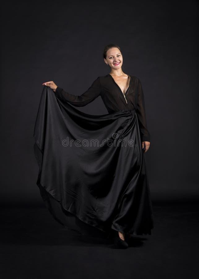 Una muchacha joven, sonriente en el traje negro que baila coreografía moderna imagenes de archivo