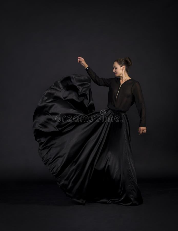 Una muchacha joven, sonriente en el traje negro que baila coreografía moderna foto de archivo