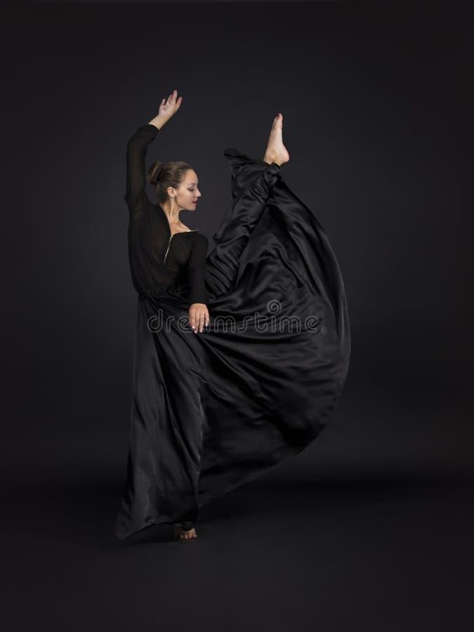 Una muchacha joven, sonriente en el traje negro que baila coreografía moderna foto de archivo libre de regalías
