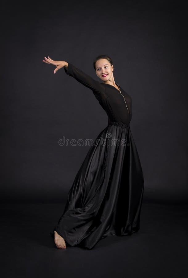 Una muchacha joven, sonriente en el traje negro que baila coreografía moderna fotos de archivo