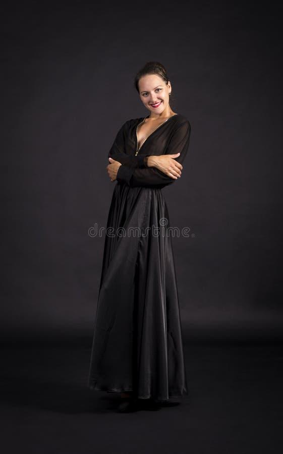 Una muchacha joven, sonriente en el traje negro que baila coreografía moderna fotografía de archivo libre de regalías