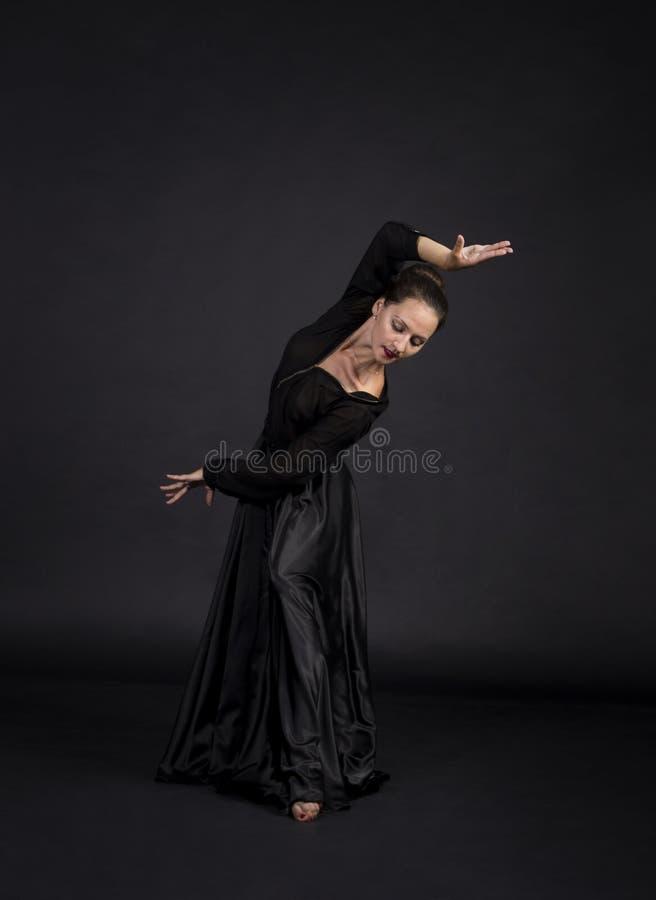 Una muchacha joven, sonriente en el traje negro que baila coreografía moderna imágenes de archivo libres de regalías