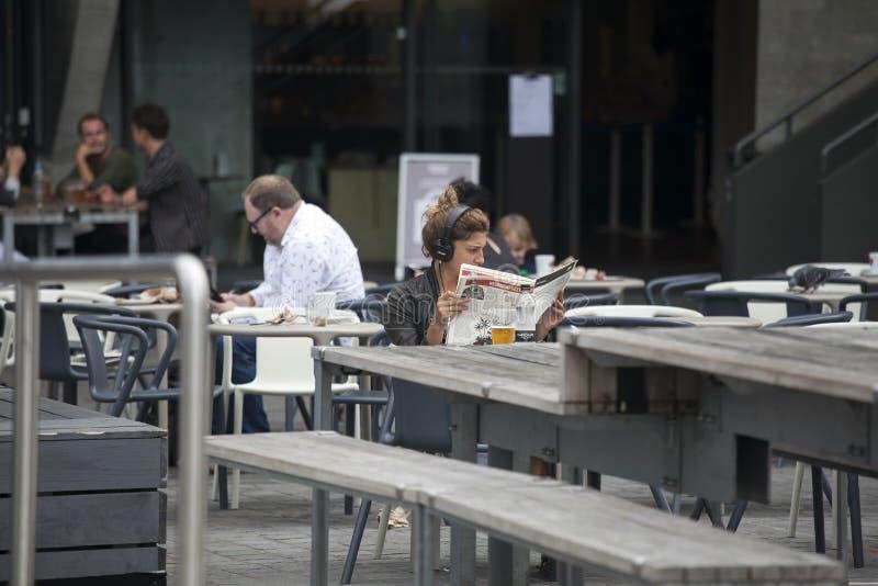 Una muchacha lee una revista, escucha la música y bebe la cerveza en un café imagen de archivo
