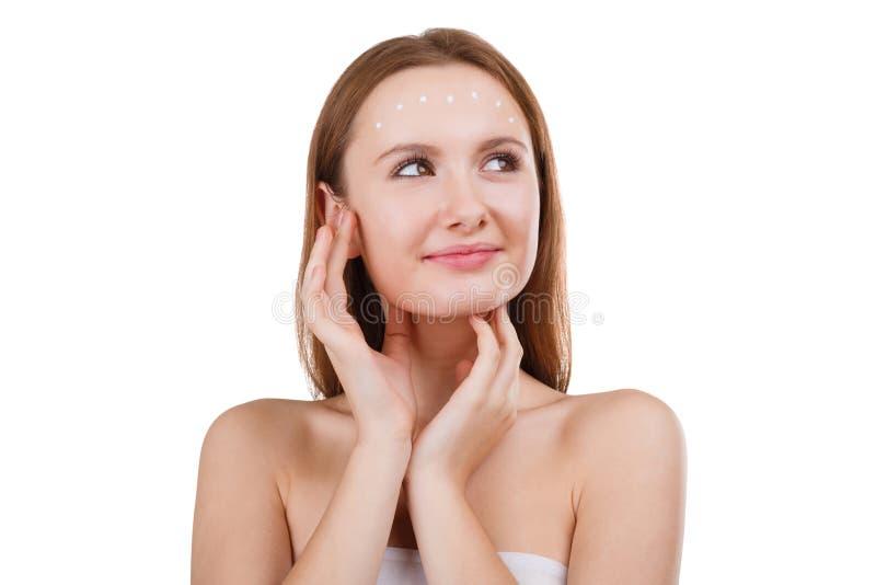 Una muchacha linda aplica una crema cosmética en cara y mira para arriba con una sonrisa El concepto de belleza Aislado fotografía de archivo libre de regalías