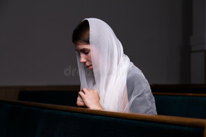 Una muchacha modesta joven con un pañuelo en su cabeza se está sentando en iglesia y está rogando El concepto de religión, rezo,  imagen de archivo