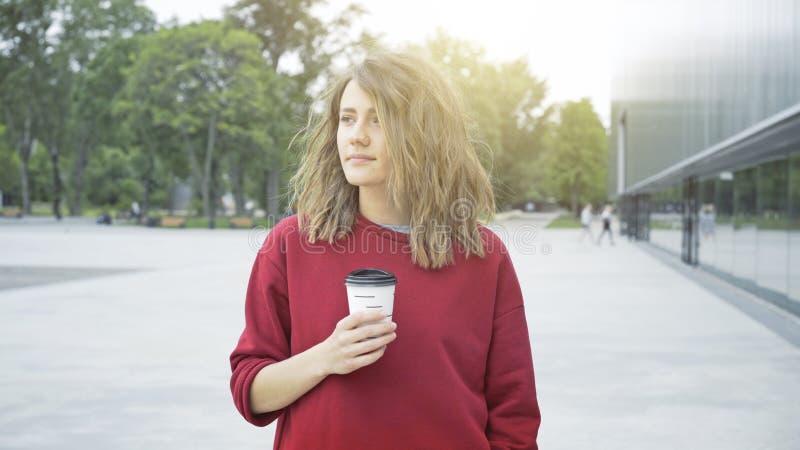 Una muchacha morena casual linda joven está bebiendo el café al aire libre por la mañana imagen de archivo