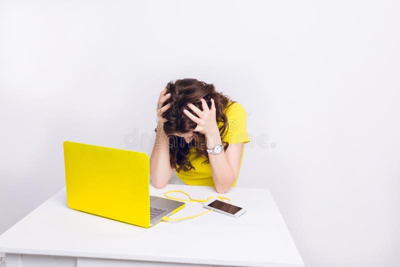 Una muchacha morena con el pelo rizado es el sentarse triste delante de un ordenador portátil en caja amarilla Ella se sienta det fotografía de archivo