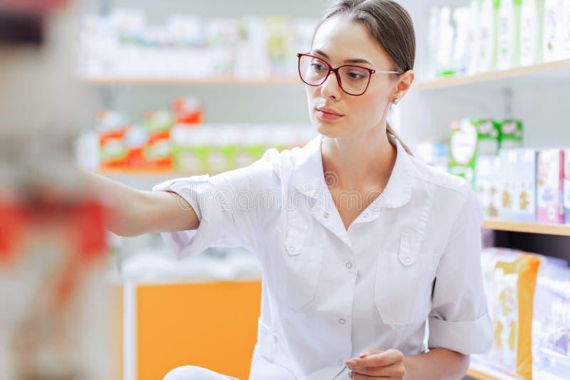 Una muchacha morena fina joven con los vidrios, vestidos en una capa del laboratorio, agachándose, toma algunas medicinas del est fotografía de archivo