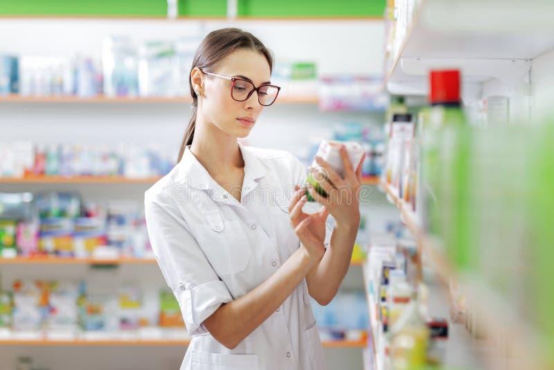 Una muchacha morena fina joven con los vidrios, vestidos en un guardapolvo médico, lee algo en el paquete de las píldoras al lado fotos de archivo libres de regalías