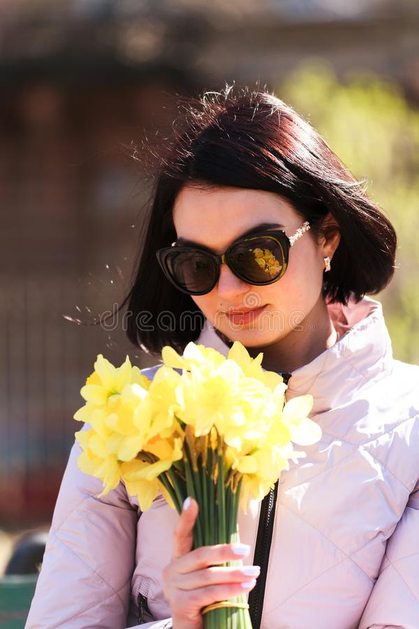 Una muchacha morena hermosa joven en las gafas de sol que sostienen un ramo de narcisos Un puñado de flores fotos de archivo libres de regalías