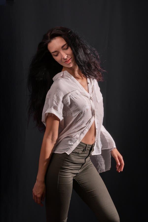 Una muchacha morena joven en una camisa blanca está bailando fotografía de archivo