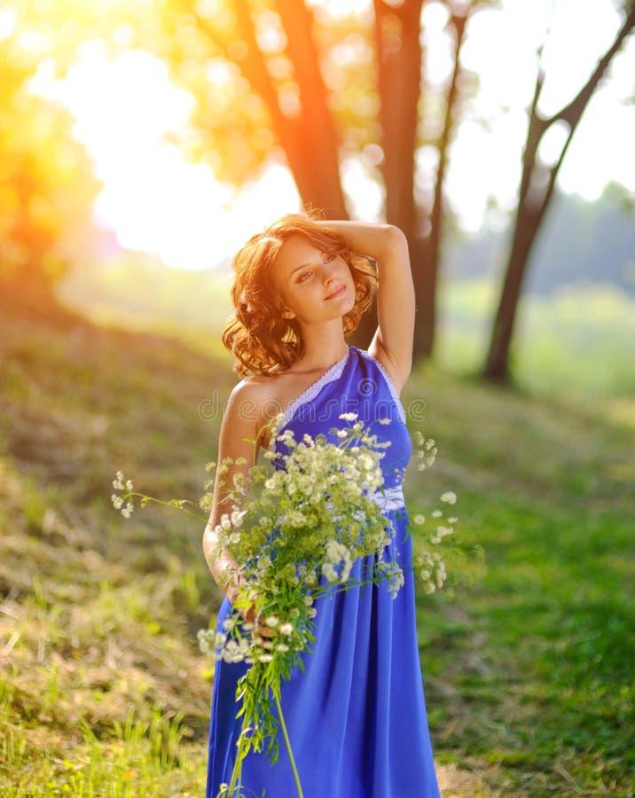 Una muchacha morena joven en un vestido azul que presenta con un ramo de flores salvajes en un parque en los rayos de un sol bril imágenes de archivo libres de regalías
